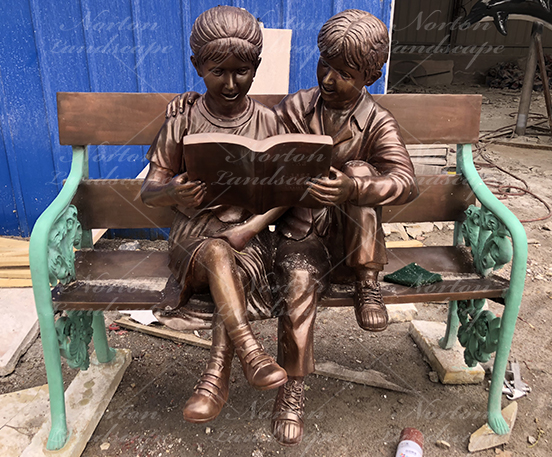 Bronze children statue sitting on bench