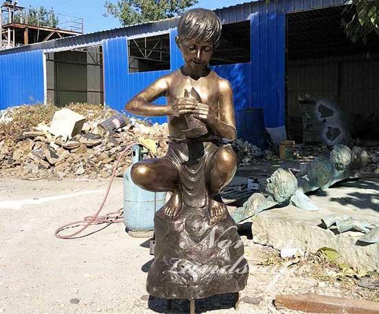 Bronze boy and fish statue