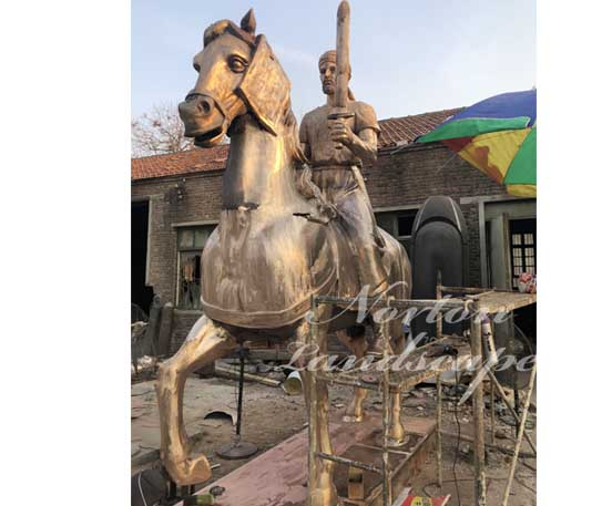 Bronze man riding horse statue